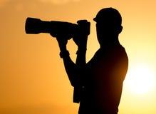 有一台照相机的人摄影师在日落 免版税图库摄影