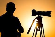 有一台照相机的人摄影师在日落 免版税库存图片