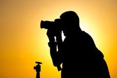 有一台照相机的人摄影师在日落 库存照片