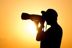 有一台照相机的人摄影师在日落 免版税库存照片