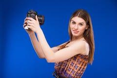 有一台照相机的女孩在他的手上 免版税库存图片