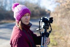 有一台照相机的妇女在三脚架 图库摄影