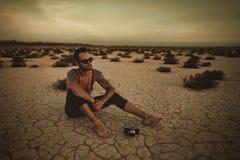 有一台照相机的摄影师在沙漠领域 库存照片