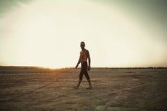 有一台照相机的摄影师在沙漠领域 免版税库存图片