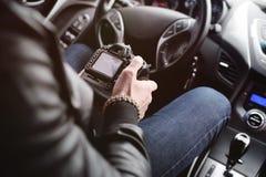 有一台照相机的年轻人在汽车 免版税图库摄影