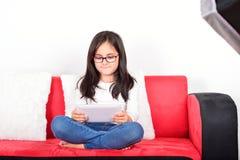 有一台片剂个人计算机的女小学生在照片演播室 库存照片