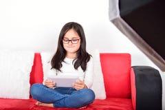 有一台片剂个人计算机的女小学生在照片演播室 免版税库存照片