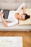 有一台片剂个人计算机的少妇在沙发 免版税库存照片