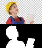 有一台片剂计算机的女性建筑工程师在工地工作,阿尔法通道 免版税库存图片