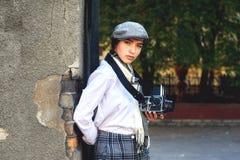 有一台老照相机的女孩摄影师在他的手上 库存图片