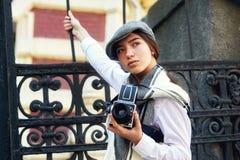 有一台老照相机的女孩摄影师在他的手上 免版税图库摄影