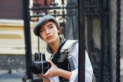 有一台老照相机的女孩摄影师在他的手上 图库摄影