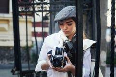 有一台老照相机的女孩摄影师在他的手上 库存照片