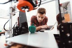 有一台膝上型计算机的一个人在他的手上控制打印3d打印机的过程 3d打印机打印了苹果的模型 免版税库存照片