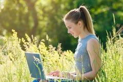 有一台膝上型计算机的一个女孩本质上在绿草中的 图库摄影