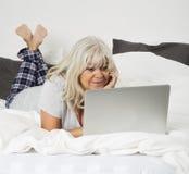 有一台膝上型计算机的中间年龄妇女在床上 图库摄影