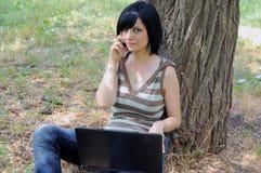 有一台膝上型计算机的女孩在公园 库存图片