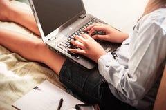 有一台膝上型计算机的女孩在卧室 免版税库存图片
