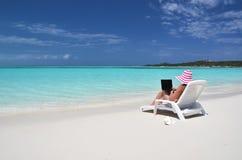 有一台膝上型计算机的女孩在热带海滩 库存图片