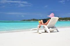 有一台膝上型计算机的女孩在热带海滩 库存照片