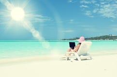 有一台膝上型计算机的女孩在热带海滩 免版税库存图片