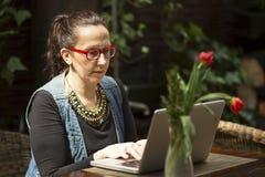 有一台膝上型计算机的女性自由职业者在夏天咖啡馆 工作 图库摄影