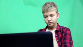 有一台膝上型计算机的少年在绿色背景 股票视频
