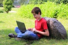 有一台膝上型计算机的少年在公园 免版税库存图片