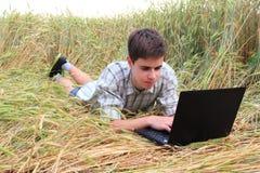 有一台膝上型计算机的少年在领域 免版税库存图片