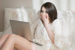 有一台膝上型计算机的惊奇的女孩在床上 库存图片