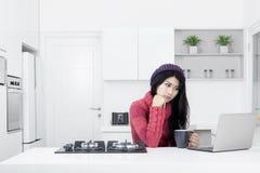 有一台膝上型计算机的沉思妇女在厨房里 免版税库存图片