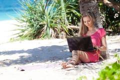 有一台膝上型计算机的白肤金发的女孩在热带海滩 免版税库存图片