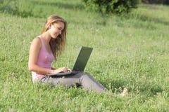 有一台膝上型计算机的美丽的少年女孩在草 库存照片
