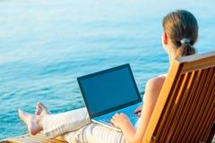 有一台膝上型计算机的赤足女孩在海滩 库存图片