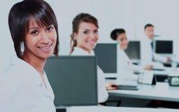 有一台计算机的女商人在有后边小组的办公室 库存图片