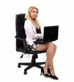 有一台计算机的女孩在一把黑椅子 免版税库存图片