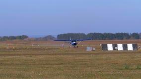有一台转动的推进器的小飞机沿有地面涂层的一条跑道移动 股票录像