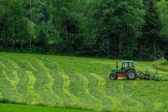 有一台转台式摊草机的拖拉机 免版税库存图片