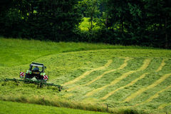 有一台转台式摊草机的拖拉机 免版税库存照片