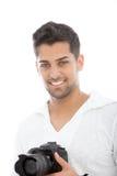 有一台dslr照相机的年轻人在他的手上 图库摄影