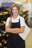 有一名微笑的职员的妇女的画象在她的手上的一张剪贴板 免版税库存图片