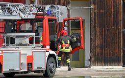 有一名消防队员的消防车在一次紧急呼叫期间 免版税库存照片