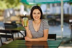 有一名绿色圆滑的人的愉快的女性 咖啡馆的华美的妇女在被弄脏的背景 夏天咖啡馆概念 复制空间 库存照片