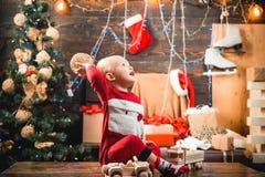 有一圣诞礼物的愉快的孩子在木背景 在圣诞老人帽子的愉快的小孩子有当前的有圣诞节 免版税库存图片