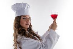 有一块大玻璃的o女孩厨师 免版税库存照片