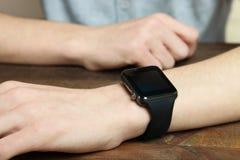 有一块巧妙的手表的一只人` s手 库存图片