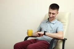 有一块巧妙的手表的人 库存图片