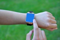 有一块巧妙的手表的手 库存照片