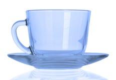 有一块板材的蓝色空的杯子在白色背景 图库摄影