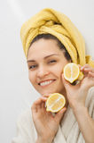 有一块毛巾的一个女孩在她的头举行柠檬的两个一半 库存照片